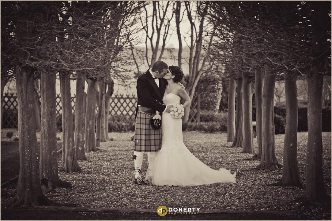 Fawsley Hall wedding couple kissing in gardens