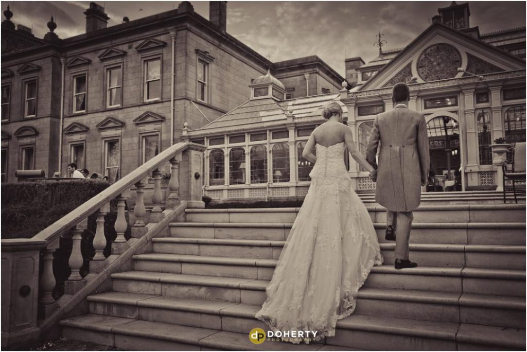 Bride and groom walk up step at Kilworth House