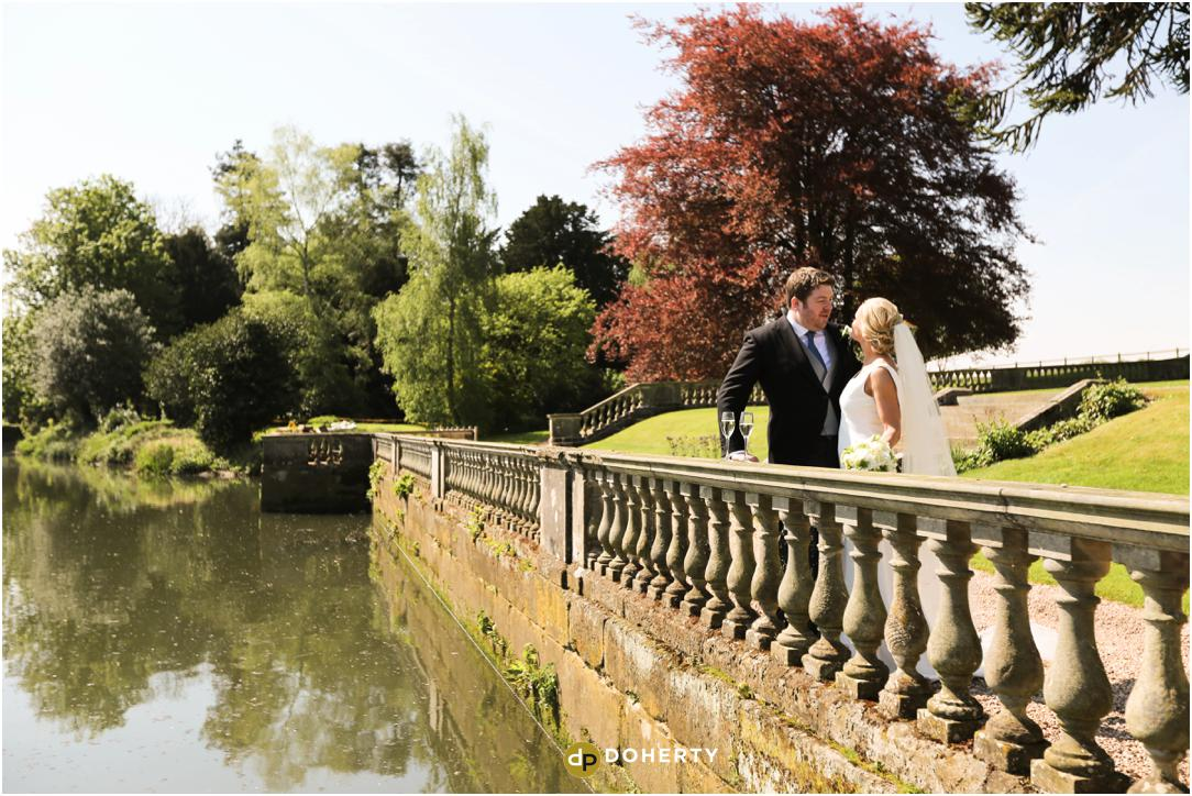 Bride and Groom beside river at Stoneleigh Abbey