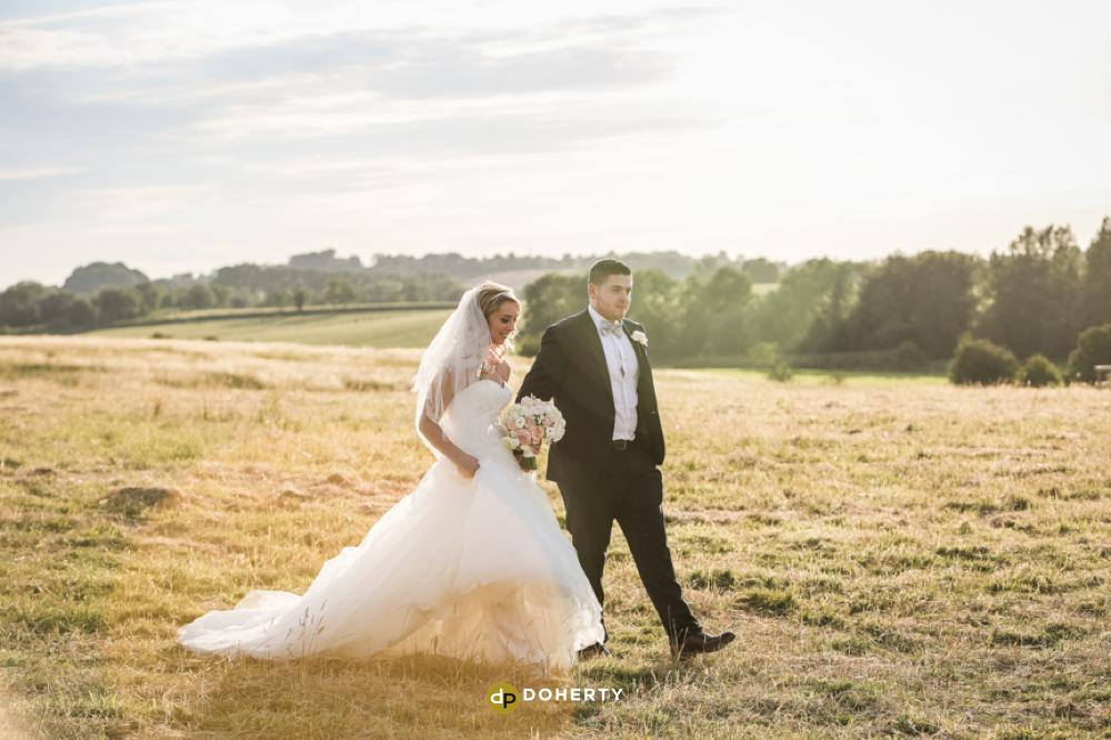 Bride and groom walking in fields atDodford Manor - Wedding Photography