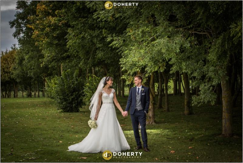 Bride and Groom walking in fields - Stratford Park Hotel