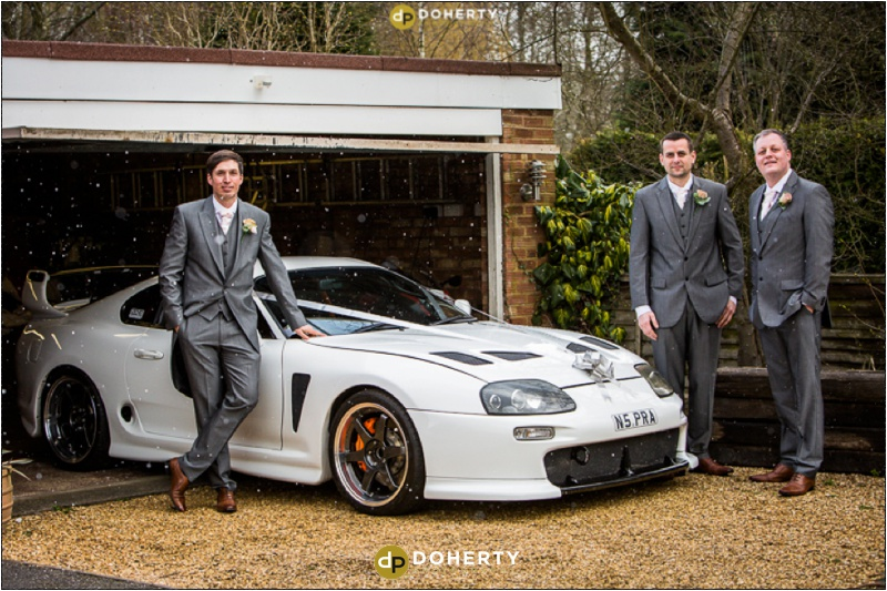 Groom with his wedding car and groomsmen