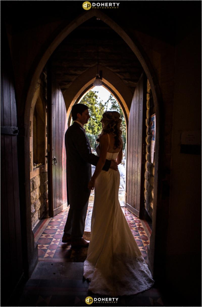 Bride and Groom exit Church in Doorway