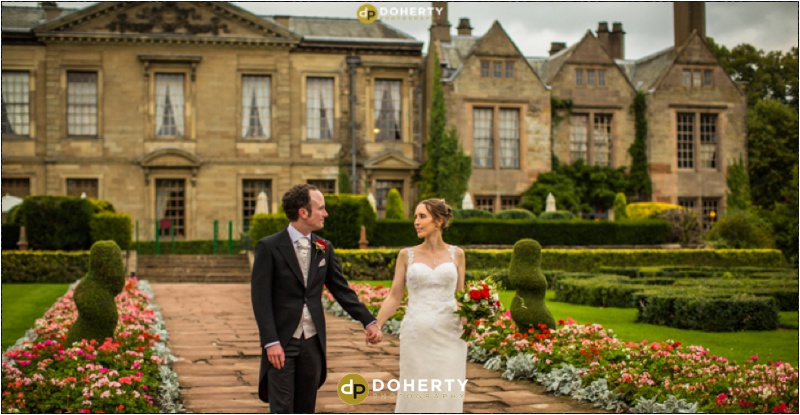 Coombe Abbey Hotel Bride and Groom walking on west terrace