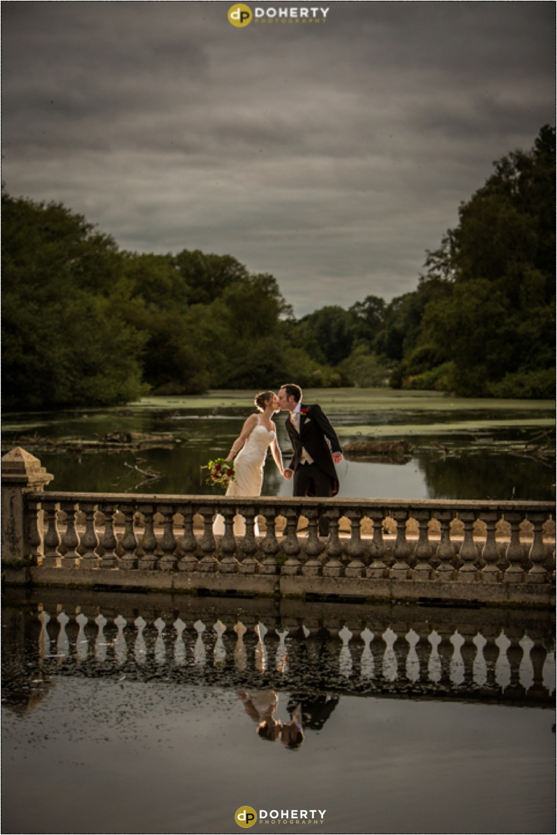 Coombe Abbey bride and groom on bridge by Lake