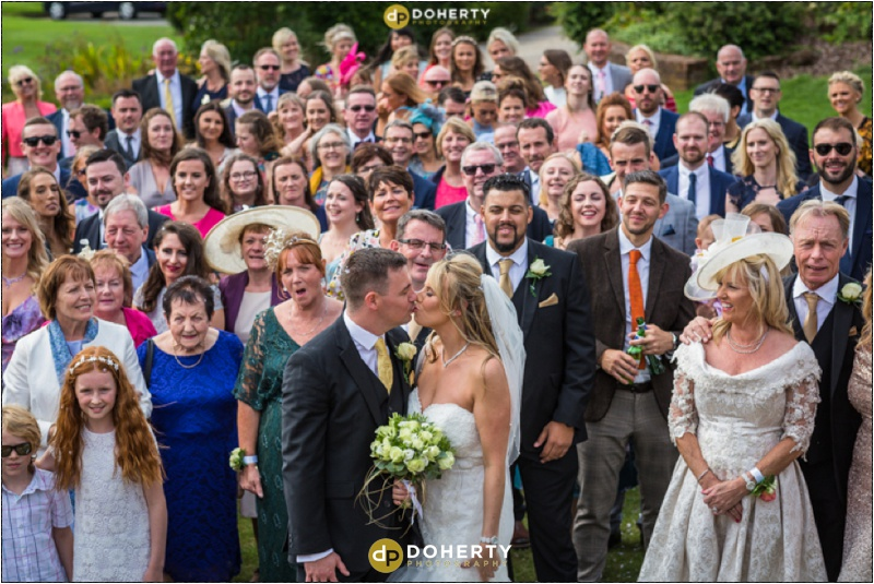 Windmill Village Wedding Kiss with group photo