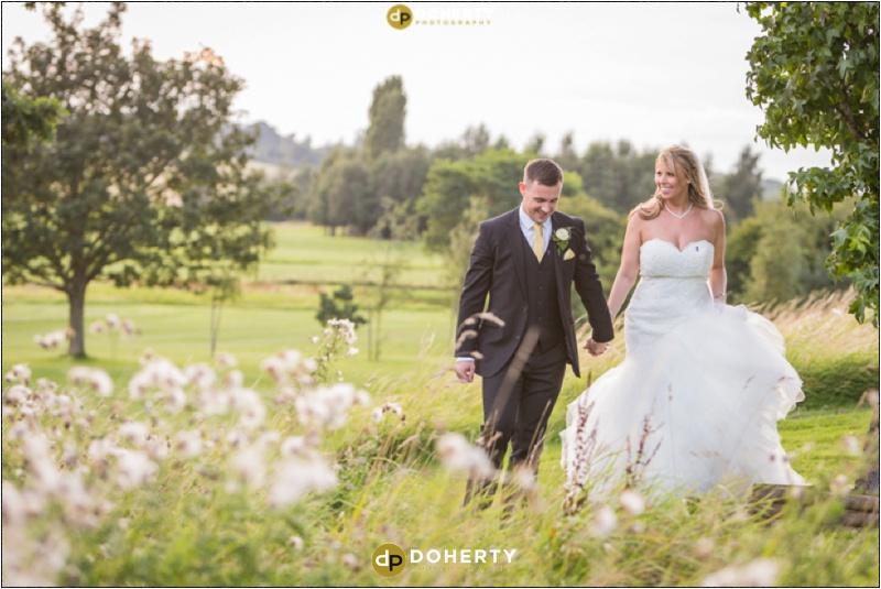 Windmill Village Wedding Bride and Groom walking in fields