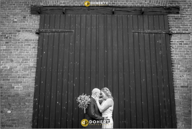 Best Western Windmill Village Bride and Groom in front of large barn doors