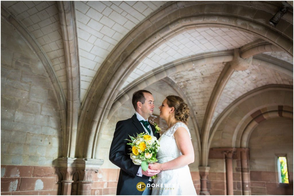 Coombe Abbey bride and groom in arches
