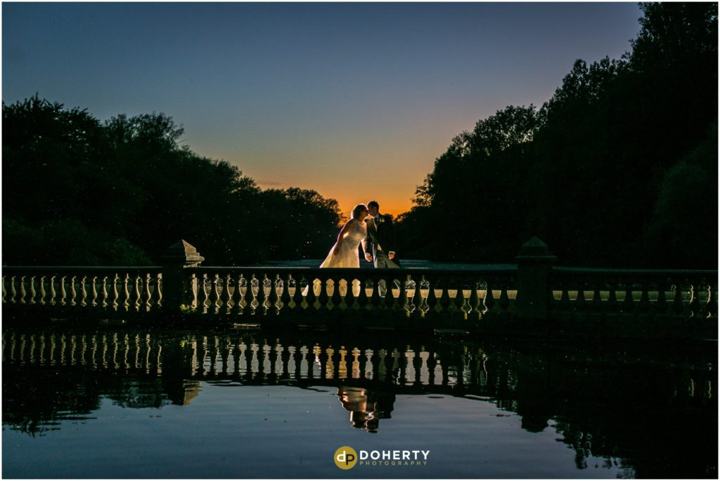 Coombe Abbey Bride and Groom on Bridge at Sunset