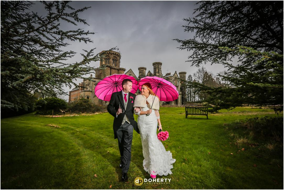 Studley Castle couple with pink umbrellas