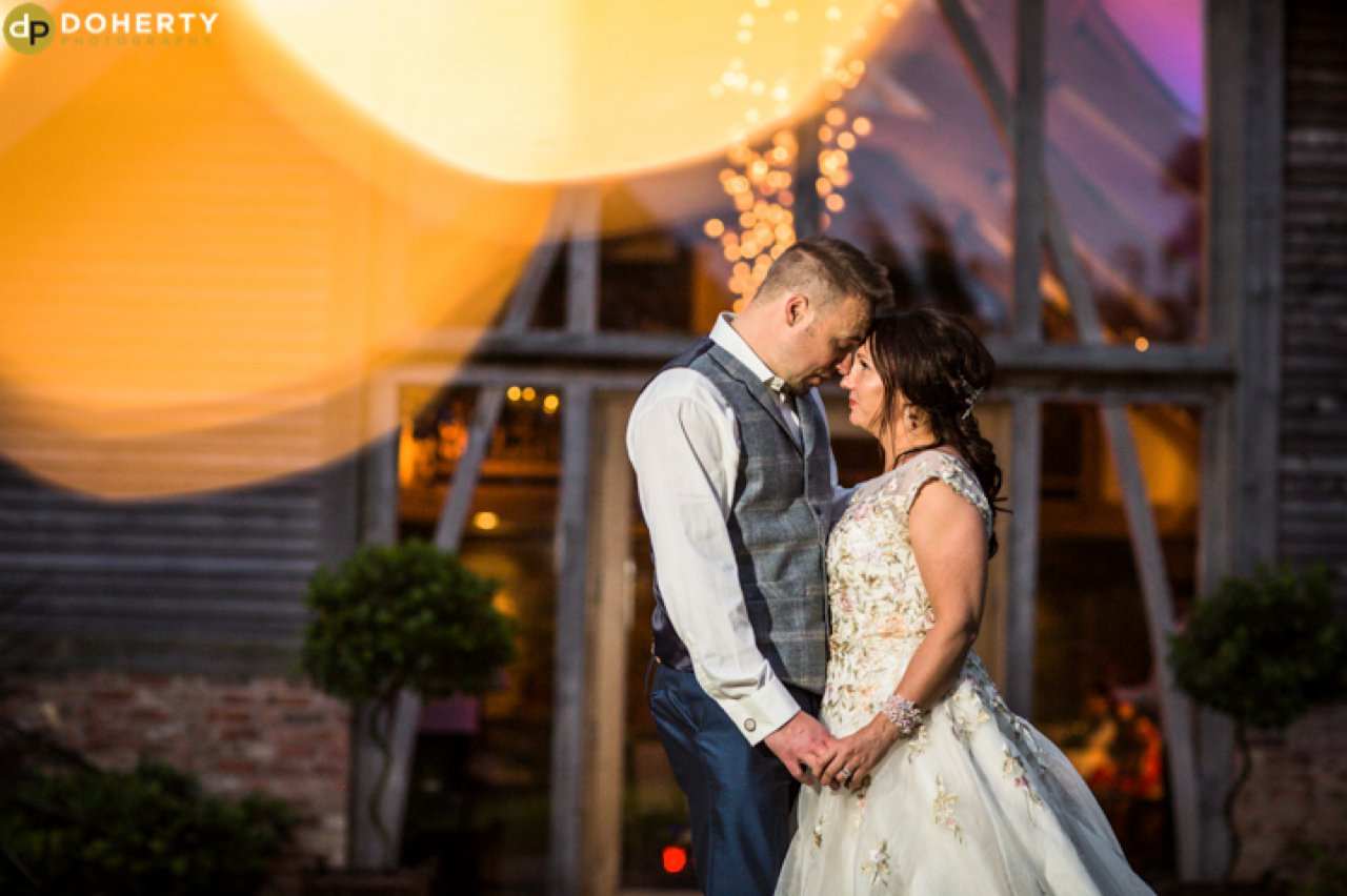 Mythe Barn at Night with bride and groom