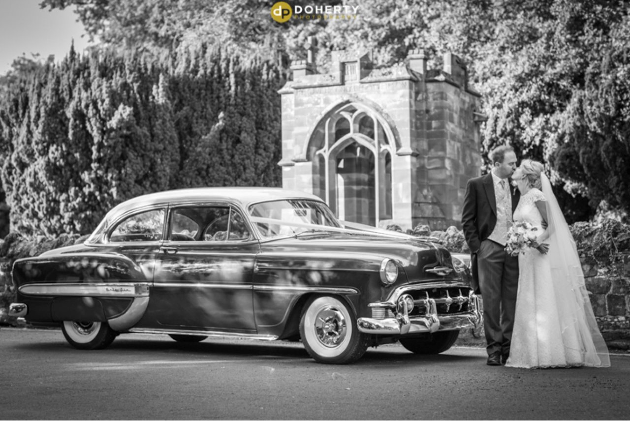 Berkswell Church with wedding car and bride and groom