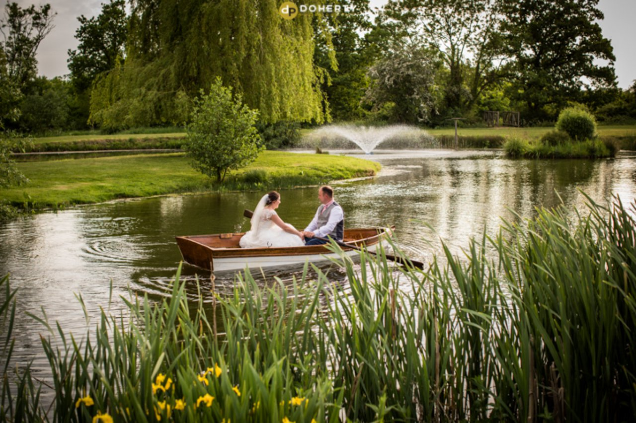 Bride and Groom on Boat on lake at Wootton Park