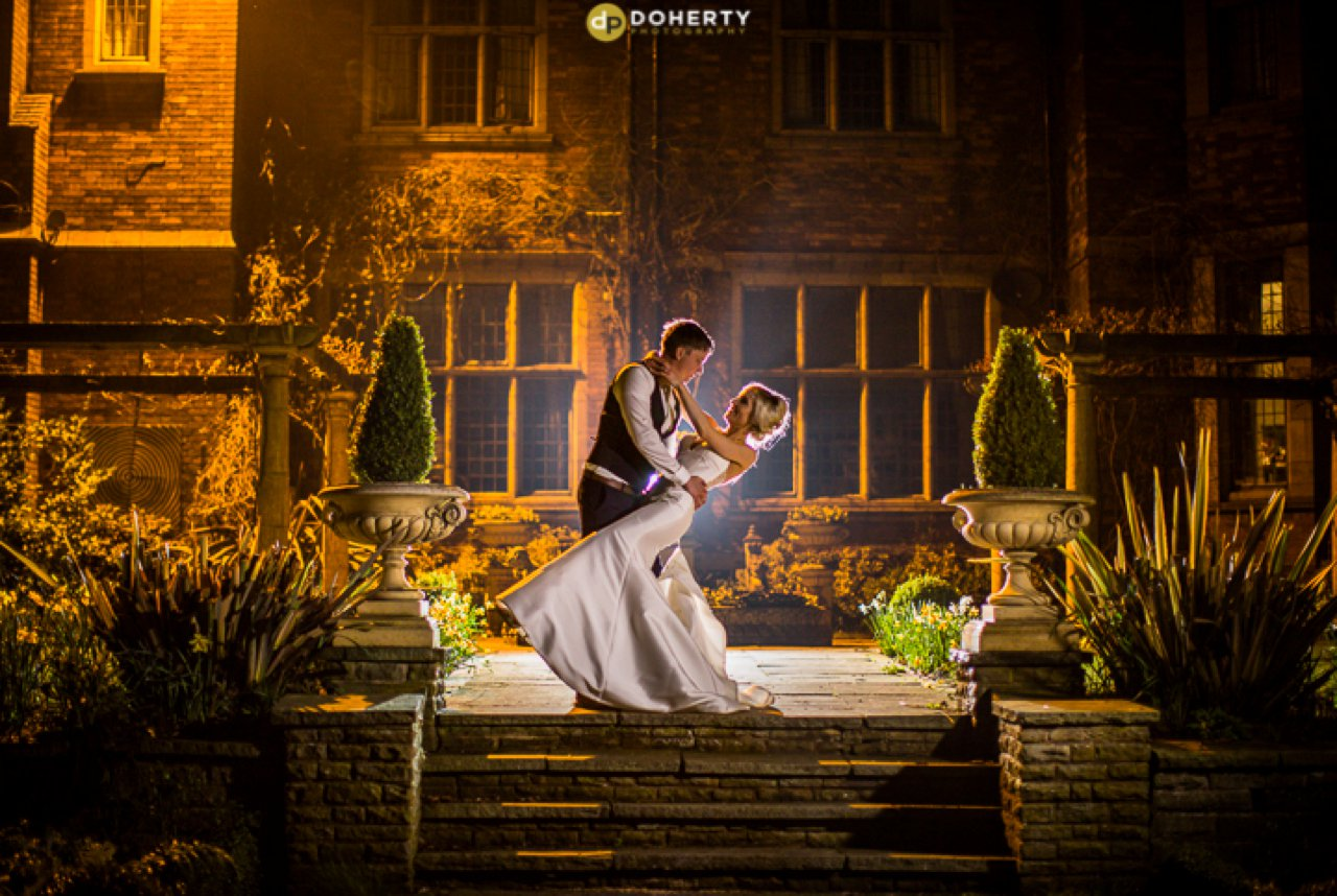Moxhull Hall at night with bride and groom