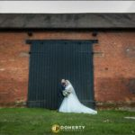 Bride and groom beside barn doors