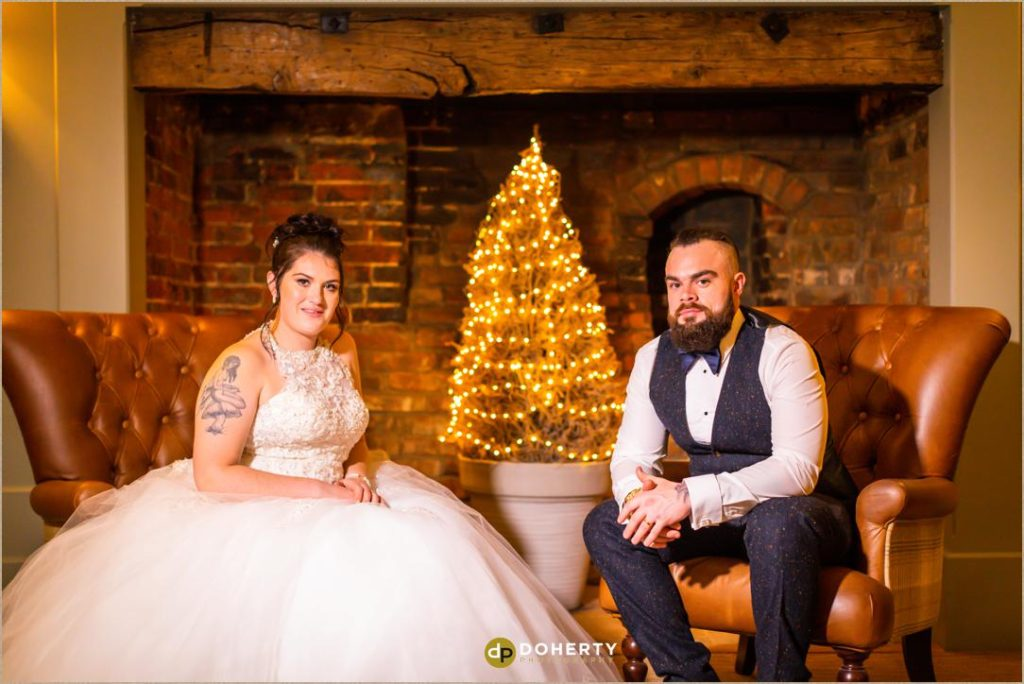 Bride and Groom seated at fireplace