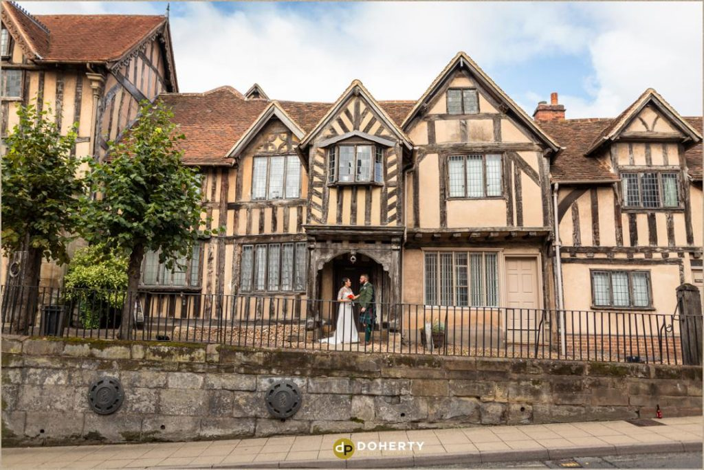 Wide shot of bride and groom outside lord Leycester in Warwick