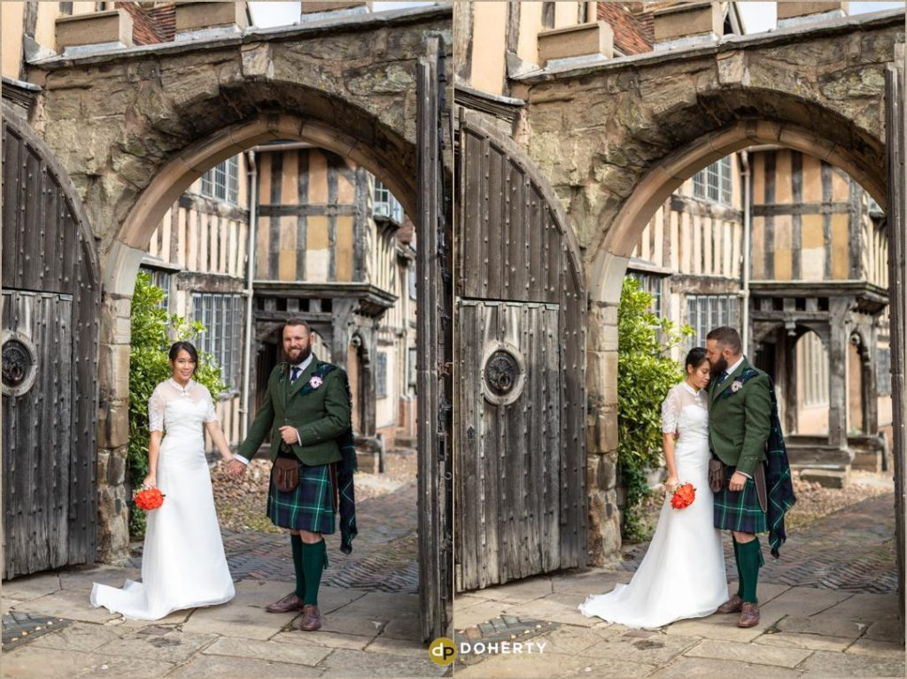 Bride and groom on archway at Lord Leycester Hospital