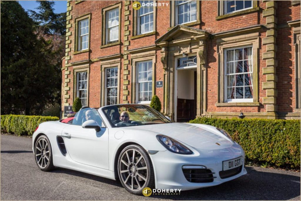 Groom arrives in white Porsche for wedding at Ansty Hall
