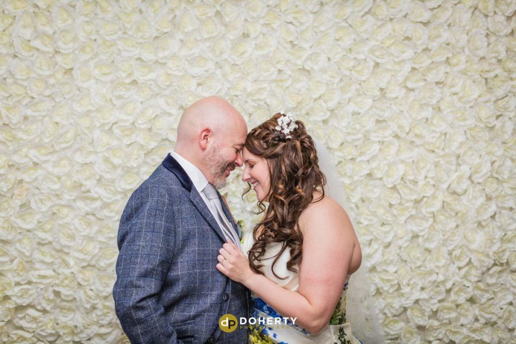 Bride and Groom in front of flowered wall at Ansty Hall