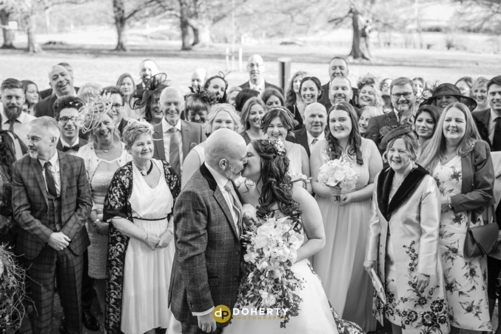 Bride and groom kiss with guests watching on at Ansty Hall