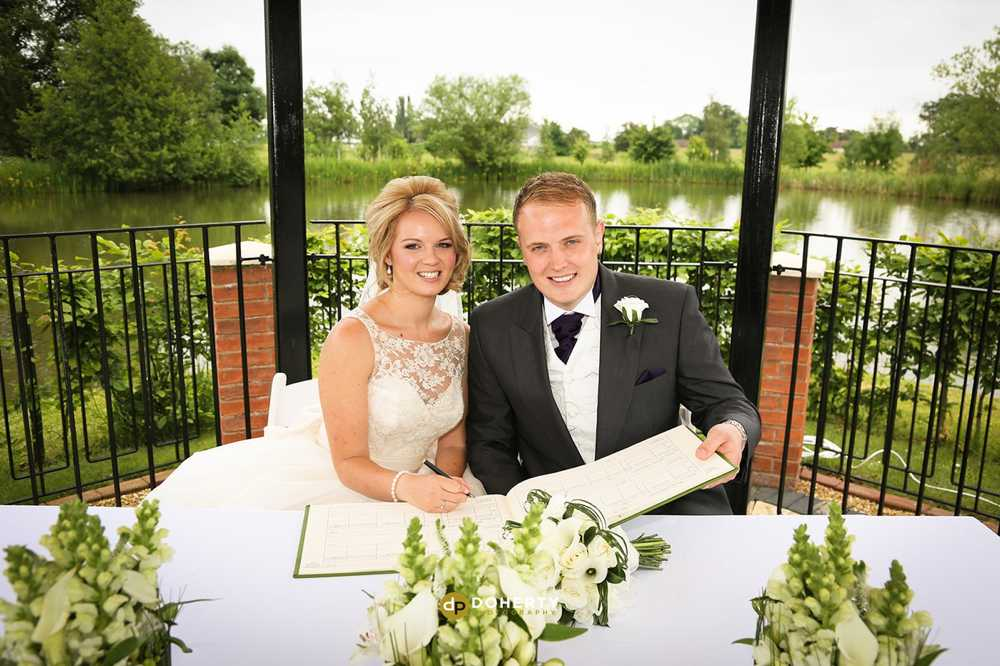 Ardencote Manor wedding couple signing registrar
