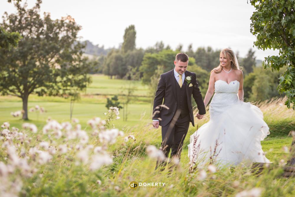 Windmill Village bride and groom walking in fields