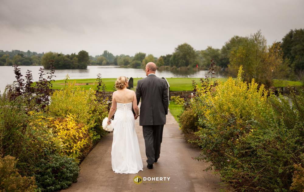 The Lake at Barston wedding with bride and groom walking by lake