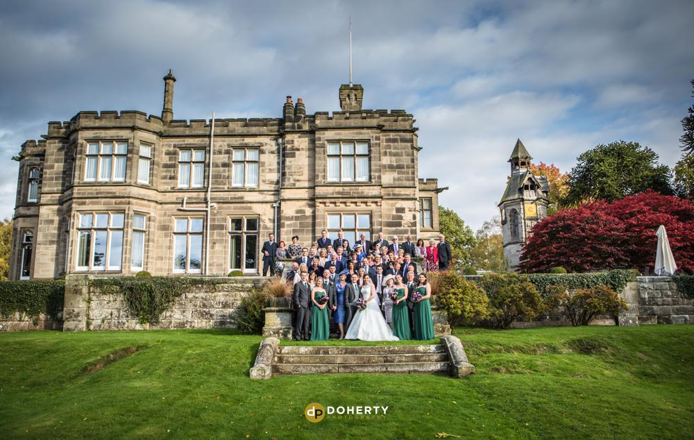 Group photo at Hampton Manor with venue as backdrop