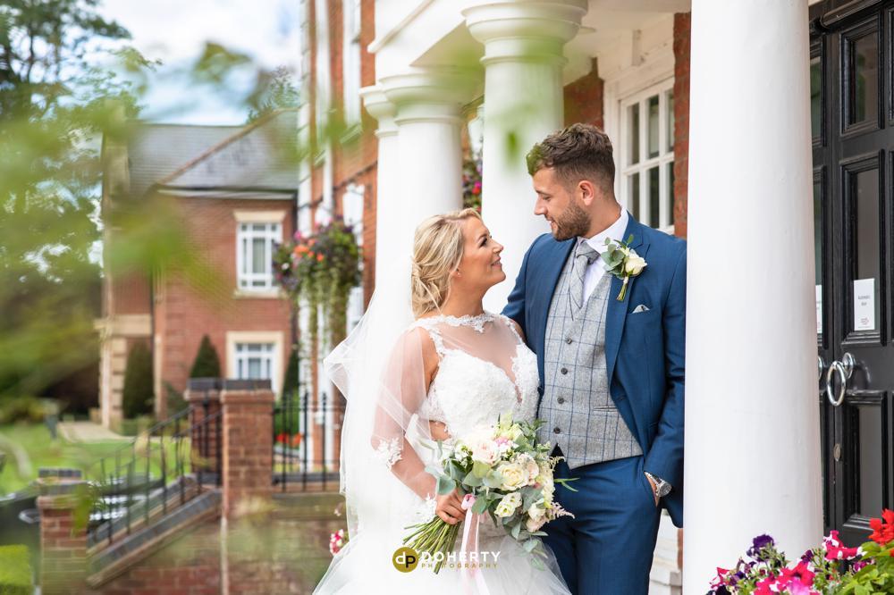 Bride and groom at entrance of Manor Hotel Meriden