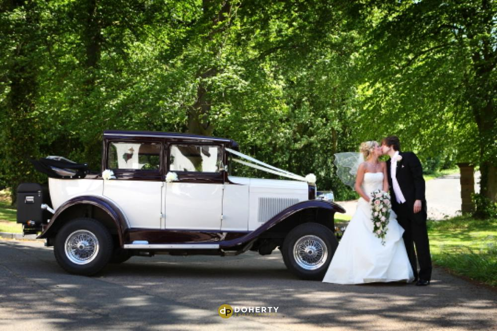 Bride and groom with wedding car at Ullesthorpe Court in Leicestershire