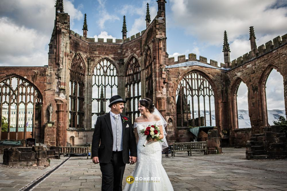 Bride and Groom walking in Coventry Cathedral ruins on wedding day