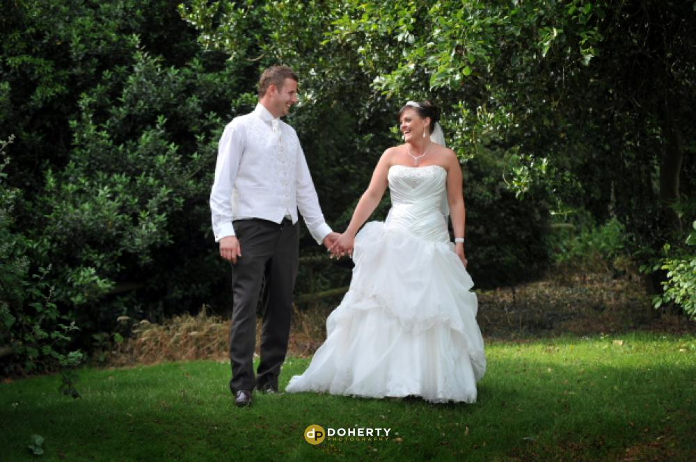Bride and groom walking in gardens at Honiley Court Hotel