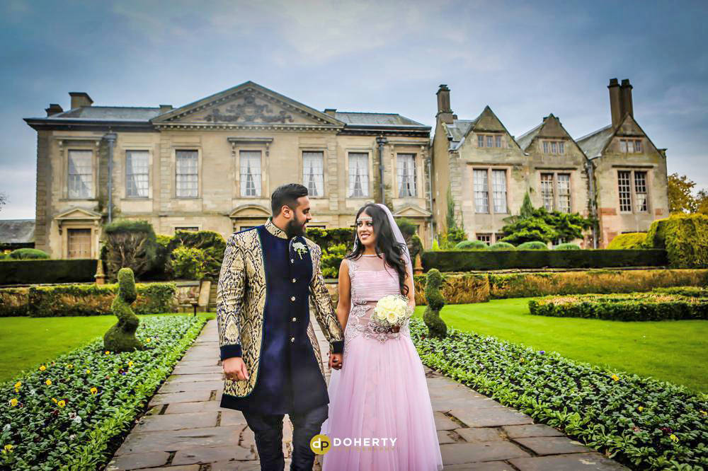 Asian wedding couple walking in grounds
