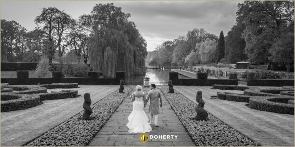 Fusion Wedding Photography - Coombe Abbey with bride and groom walking in gardens