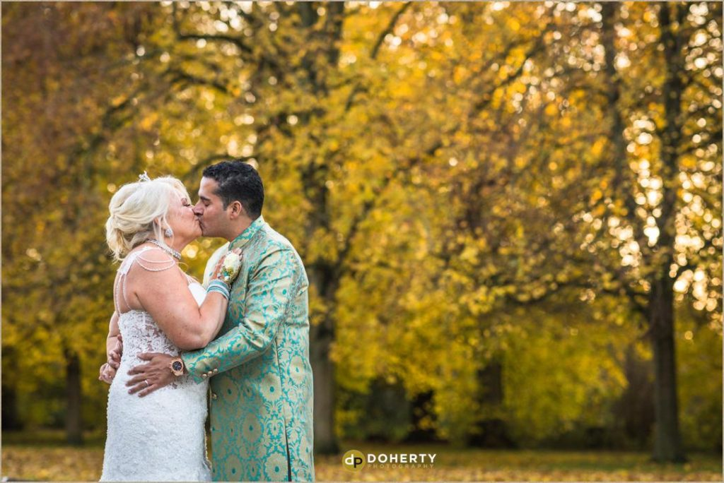Coombe Abbey at autumn with bride and groom