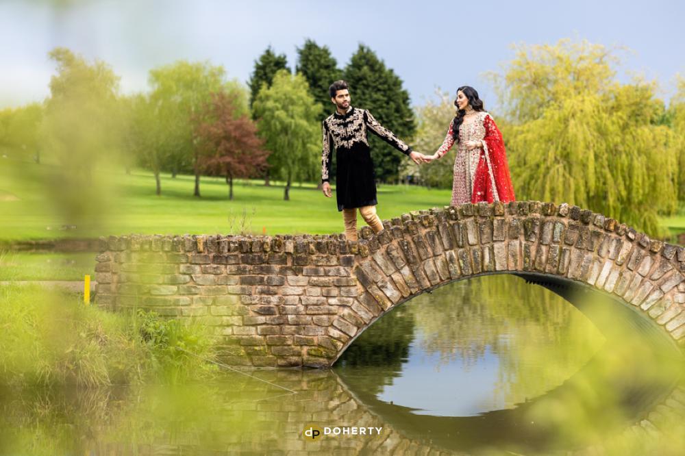 asian wedding bride and groom walking over a bridge