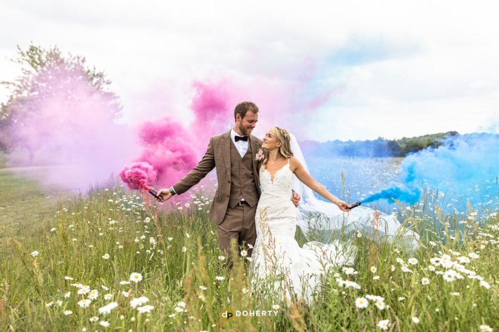 Bride and Groom with smoke Bombs in a field at a wedding