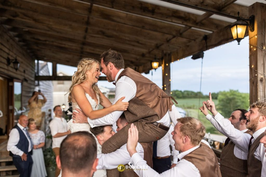 Outdoor Partying photo at Crockwell Farm. Bride and Groom on shoulders of groomsmen