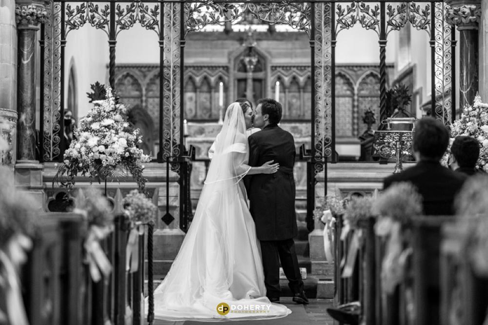 bride and groom kiss at St John the Baptist church at Hagley Hall
