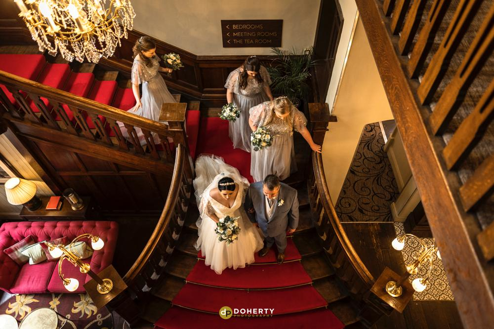 Bride and bridesmaids on staircase at Iliffe Hotel in Coventry