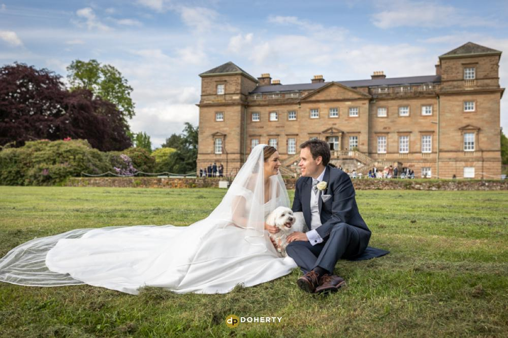 Bride and groom with dog sitting in grounds at Hagley Hall