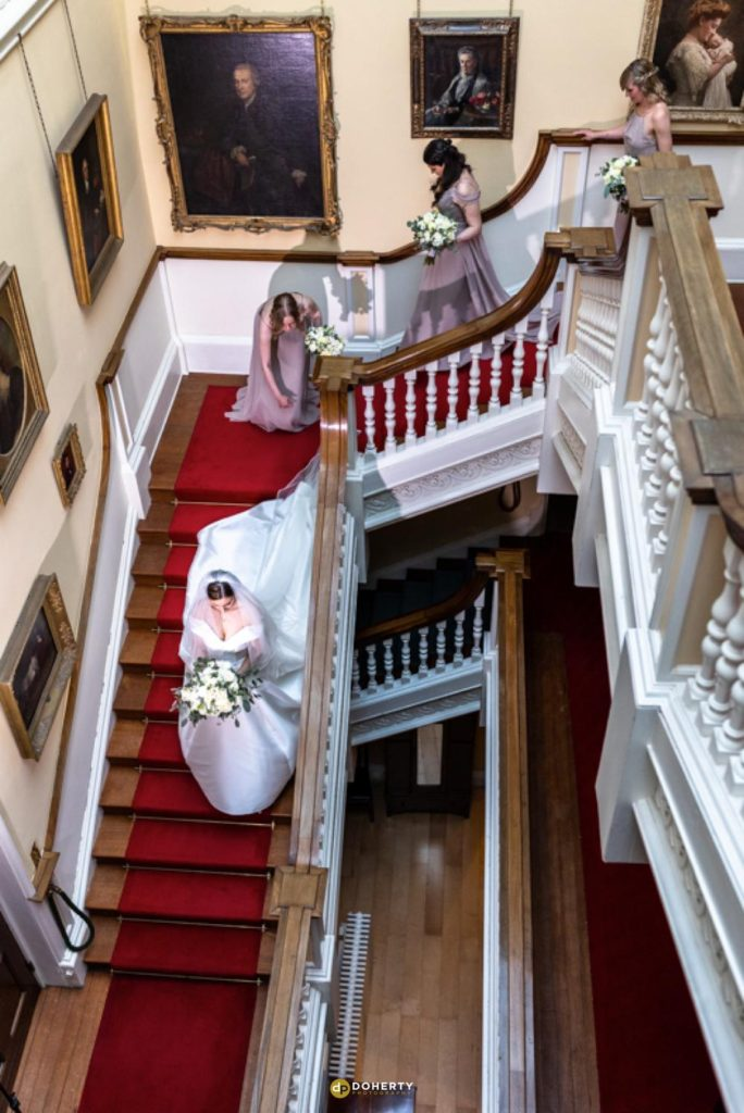 Bride walking down stairs at Hagley Hall in Stourbridge