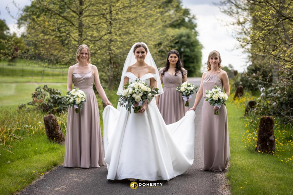 Bridesmaids walk to church at Hagley Hall in West Midlands